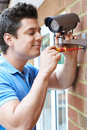 Security Consultant Fitting Camera To House Wall Royalty Free Stock Photo