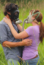 Security in dangerous times a loving affectionate couple with gas masks standing the tall grass allergies bad breath or for the Stock Photos