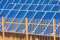 Security fence prevents unauthorised access to solar power electric generating system and facility. Dusty solar panels surface