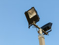 Security floodlights on a tall post against a winter blue sky at Royalty Free Stock Photo