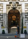 A security man stands on the doorway to a luxurious gothic entrance to a building Royalty Free Stock Photo