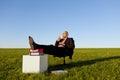 Sedia di enjoying coffee on dell uomo d affari nel campo erboso contro il cielo Immagini Stock Libere da Diritti