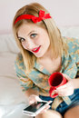 Seductive beautiful pinup blond young woman blue eyes girl sitting in bed with mobile cell phone and red cup happy smiling looking Royalty Free Stock Photo