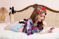 Seductive, beautiful pinup young woman relaxing in bed with mobile cell phone and red cup happy smiling & looking up at copyspace Royalty Free Stock Photo