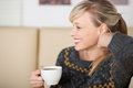 Seductive blond woman playing with her hair smiling and while drinking a cup of coffee Royalty Free Stock Photos