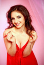 Seductive brunette woman red lingerie pink background Royalty Free Stock Image