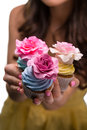 Seductive confection in macro sweet cupcakes with marchpane roses and a lot of cream of different colors yummy cupcakes Royalty Free Stock Photo
