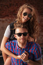 Seductive couple of happy young people in love posing outdoors over brick wall Stock Photography