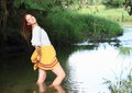 Seductive girl in skirt in water young woman smiling standing of stream Stock Photo