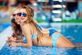 Seductive girls enjoy summer in pool vacation Stock Images