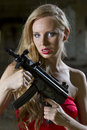 Seductive spy with automatic gun woman in red dress in old fabric Royalty Free Stock Image