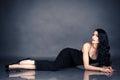 Seductive woman in black dress lying on the floor