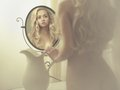 Seductive woman in the mirror nude elegant blonde front of Stock Image