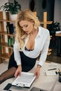seductive woman sitting on table and reading documents Royalty Free Stock Photo