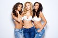 Seductive women in white bras and jeans three pretty with long wavy hair posing sexy while looking at the camera on Stock Image