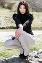 Seductive young brunette in black blouse and light pants posing on the rock Royalty Free Stock Photos