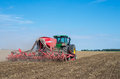 Seeder farm tractor and from the back working in a lithuanian field Royalty Free Stock Photos