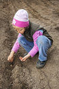 Seeding little girl planting seeds of cucumber in the field Royalty Free Stock Photography