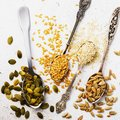 Seeds of a flax, sesame, sunflower and pumpkin in silver spoons on a table Royalty Free Stock Photo