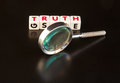 Seeking the truth text in red uppercase letters on small white cubes with a hand magnifier dark background Stock Image