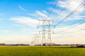 Seemingly endless row of power pylons in an agricultural landsca