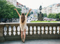 Seen from behind hippy looking woman on saint wenceslas prague longhaired tourist is standing with outstretched arms statue Royalty Free Stock Photography