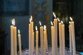 Selective focus on group of burning glowing candles light in the Royalty Free Stock Photo