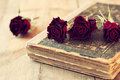 Selective focus image of dry red roses and old vintage books on wooden table. retro filtered image