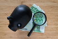 Selective focus on magnifying glass on Euro bank note with black piggy bank on wooden table as saving Royalty Free Stock Photo
