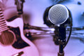 Selective focus microphone and blur electric guitar background. Royalty Free Stock Photo
