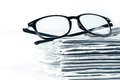 selective focus on reading eyeglasses with stacking of newspaper Royalty Free Stock Photo