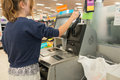 Self checkout at department store girl paying for purchases using Stock Photo