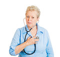 Self checkup closeup portrait senior mature woman business person worker listening to her heart with stethoscope isolated on white Royalty Free Stock Photos
