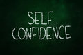 Self confidence lettering written with chalk on blackboard Stock Images