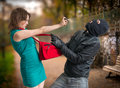 Self defense concept. Young woman was attacked by man in balaclava is using pepper spray Royalty Free Stock Photo