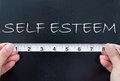 Self esteem tape measure aligned against the word handwritten on a chalkboard Stock Image