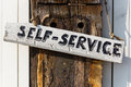 Self service sign hand written on a weathered oaken pole Stock Image