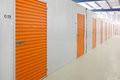 Self storage units a perspective view of a row of with closed orange doors Royalty Free Stock Photo