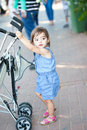Self sufficient little girl moving her carriage by herself alone in the street Stock Photography
