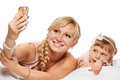 Selfie from bedtime daughter and mother are happy together making with smartphone freetime in bed on white background Royalty Free Stock Photography