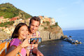 Selfie couple taking picture in cinque terre italy with smartphone self portrait photo on holidays travel young men Royalty Free Stock Photography