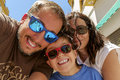 Selfie family having fun wearing sunglasses waving to a camera taking photograph on summer holiday Royalty Free Stock Photography