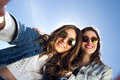 Selfie girls taking photos with a smartphone two sunglasses Stock Image