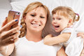 Selfie on pillow daughter and mother are happy together making with smartphone freetime in bed Stock Image