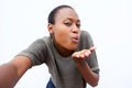 Selfie portrait of young african woman blowing a kiss Royalty Free Stock Photo