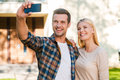 Selfie for their family album cheerful young couple bonding to each other while making by smart phone while standing against new Stock Photo