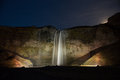 Seljalandsfoss waterfall in south iceland is lit up during the long winter nights Royalty Free Stock Photography