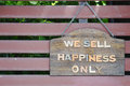 We sell happiness only signage on timber plates and timber slat background Stock Image