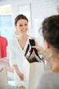 Seller in clothing store thanking the customer giving bag to Royalty Free Stock Photos