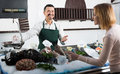 Seller and customer in fishery helping choosing chilled fish Royalty Free Stock Photos